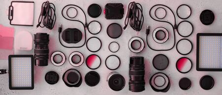Banner flat lay toned pink equipment for professional photographer on grey. Photo gradient filter, macro rings, polarizing filter, charger, video light with color plates, lens caps all for cameras