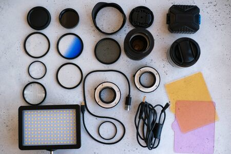 Flat lay composition equipment for professional photographer on grey. Photo gradient filter, macro rings, polarizing filter, charger, video light with color plates, lens caps all for cameras