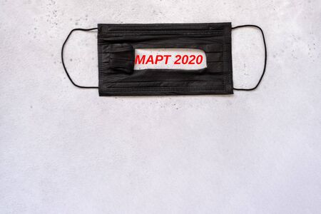 medical protective disposable black mask with text on the slot in Russian meaning march 2020 in red. concept protection of dangerous 2019-nCoV