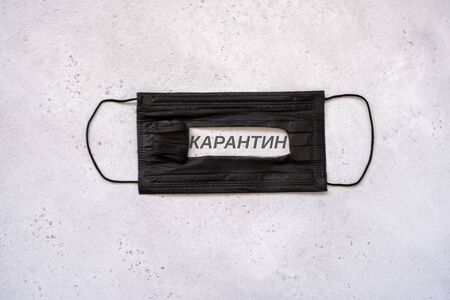 medical protective disposable black mask with text on the slot in Russian meaning the word quarantine in dark grey. concept protection of dangerous 2019-nCoV influenza coronavirus