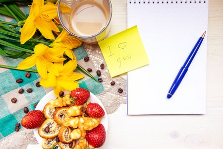 Valentines day strawberry cookies hearts with coffee, with yellow flowers on a napkin, Notepad with a pen, a note with the text Good morning, I love you happy holiday mother woman Easter