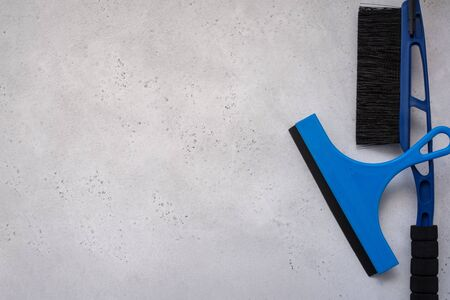 Auto accessories, layout, concept car, winter, goods store, a water pump for driving water, a snow brush and a scraper for cleaning car windows. Flat lay. Top view.