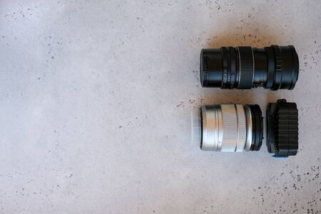 One old vintage retro style lens with one new and a box with flash drives on grey backgrond. Flat lay composition with equipment for professional photographer