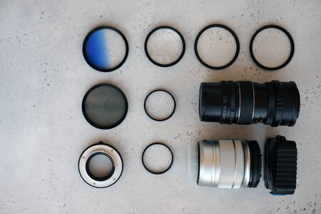 Two lenses and filters to them, adapter rings and a box with flash drives on grey backgrond. Flat lay composition with equipment for professional photographer