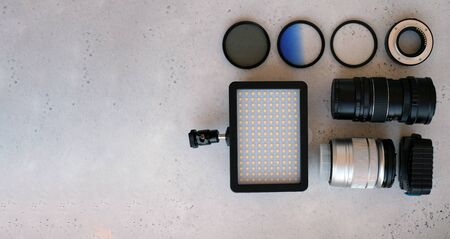 Video light, lens filters, including polarizer, gradient and adapter rings, and a box with flash drives on grey backgrond. Flat lay composition with equipment for professional photographer