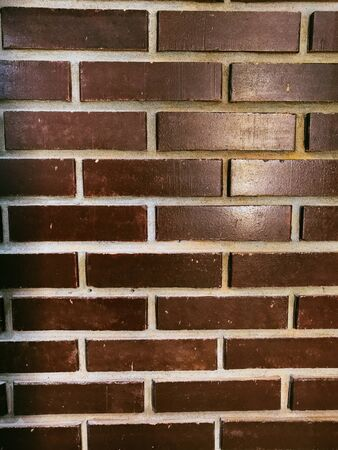 smooth wall of dark red brick. Red brick wall background. Texture of a brick wall with cracks and scratches.