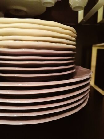 stack of plates on a dark background. Big stack of different colors mugs and plate, one above the another