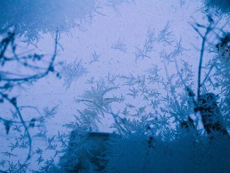 winter through frozen glass abstract background. wintry frosty pattern on glass. abstract background of ice frozen window. winter day, sun shine through frosted glass on window.