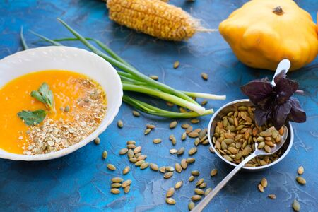 pumpkin soup with green parsley and young green onion feathers with pumpkin and corn in the background, with toasted pumpkin seeds decorated with purple Basil on a rich blue background Imagens