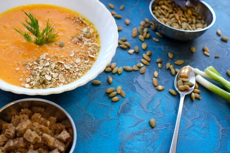 pumpkin soup with dill and young green onion feathers with toasted bread slices and pumpkin seeds decorated with purple Basil on a rich blue background Imagens