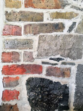the wall is made of different stones and bricks, natural and varied texture background.