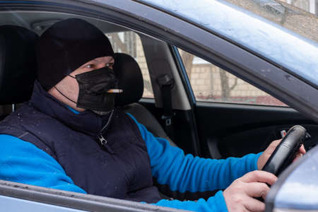 Smoking. Closeup man with mask during COVID-19 pandemic smoking a cigarette at the street.a man in a black coronavirus mask behind the wheel smokes a cigarette through a hole in the mask.