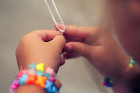 Childrens hands holding a beautiful chain with a pendant so close