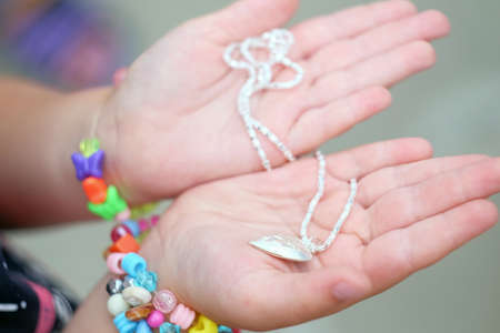 the pendant in the hands of children. Children's hands holding a beautiful chain with a pendant so close