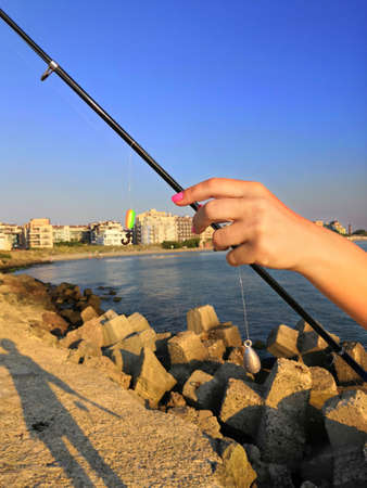women's hands impaling a worm on a hook on a fishing trip. Close-up of the hands of a fisherman who impales worms on the hook of a fishing rod on a wooden pier. Imagens