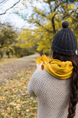 girl in a yellow scarf with maple leaves in her hands in the autumn park