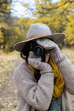 GIrl in gray hat taking pictures with a professional camera at the autumn park 写真素材