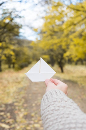 white paper boat in a hand in the autumn park leaves Stock Photo