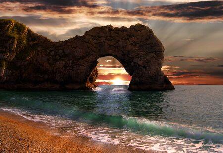 durdle: Sunrise through Durdle Door sea arch in Dorset, Jurassic Coast                     Stock Photo