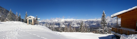 Small snowy chapelle with wooden cross in the mountains panorama