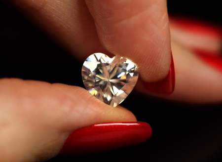diamond shape: Fingers with red nails holding heart shaped white diamond
