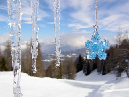 Icicles with blue crystal beads star in the mountains - blurred background photo