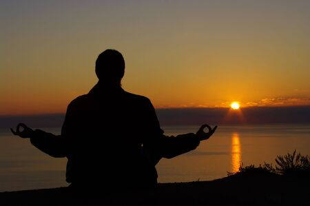 Silhouette of a man in a lotus position