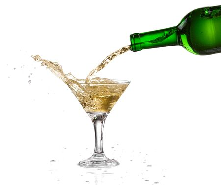 White wine pouring from the bottle intro the glass on white background Stock Photo