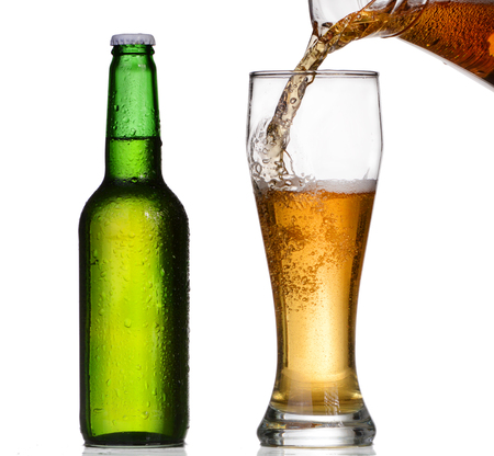 Beer pouring in a glass from a green bottle