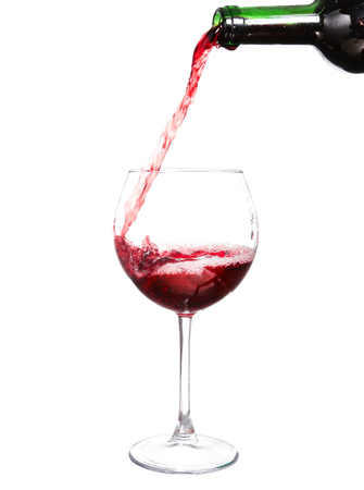 Red wine pouring on white background Stock Photo
