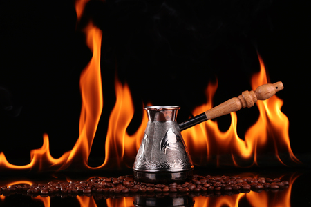 vigor: Turk on coffee beans on a background of fire, black background. CONCEPT vivacity and energy