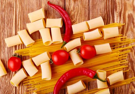 macarrones: collage Pasta con tomates cherry y otros ingredientes en el fondo de la mesa de madera