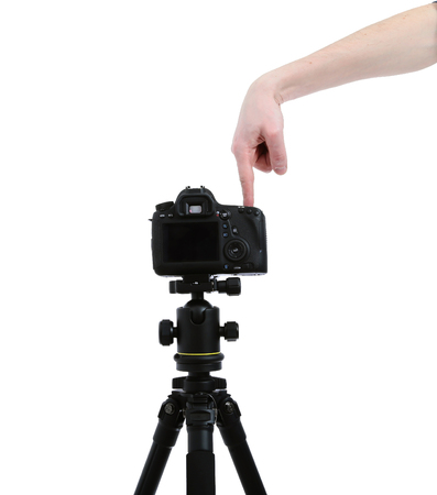 lens unit: Camera with the lens on tripod. Hand presses the shutter or remote control unit Stock Photo