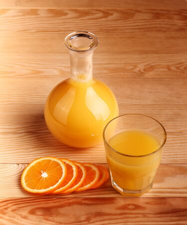 Glass of freshly pressed orange juice with sliced orange half on wooden table