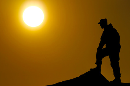 gi: Silhouette of soldier with rifle against a sunset