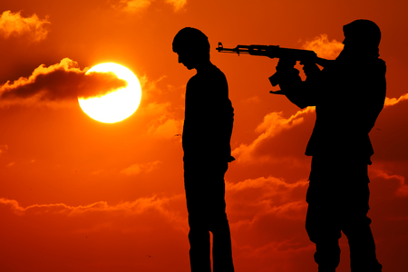Silhouette of man with rifle pointed at victims back Stock Photo