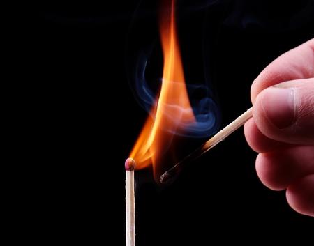 glow stick: Ignition of a match, with smoke on dark background. Hand holding burning match stick Stock Photo
