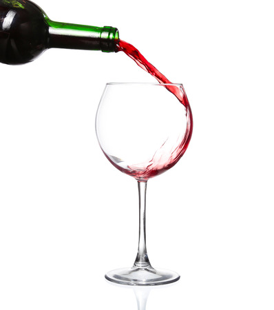 Red wine pouring from bottle into big glass on white background Stock Photo