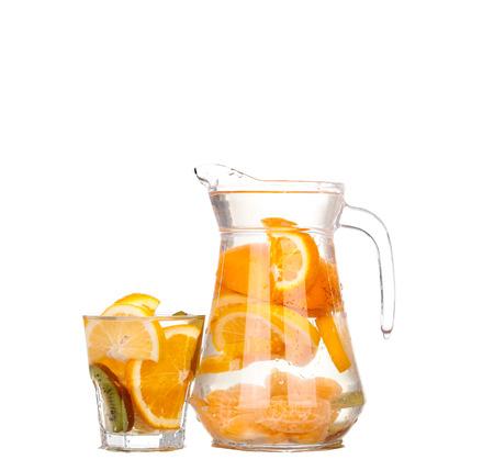 jarra con una bebida refrescante con rodajas de limón de naranja y el kiwi en el fondo blanco