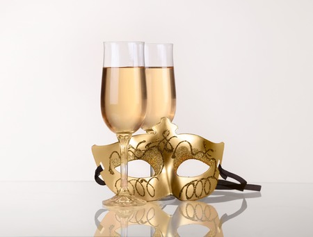 two glass with champagne on a table with Masquerade mask