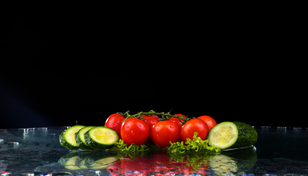 Studio shot with freeze motion of cherry tomatoes and slices of cucumber in water splash on black background, with copy space Reklamní fotografie