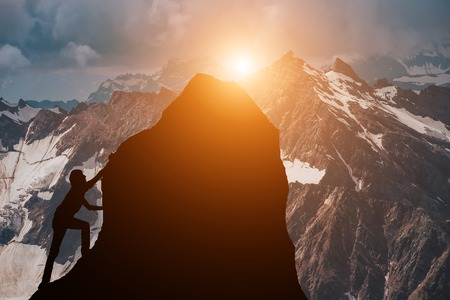 Randonneurs masculins et féminins grimpant sur la falaise de la montagne et l'un d'eux donnant un coup de main. Personnes aidant et concept de travail d'équipe.
