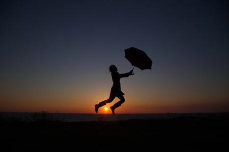 silhouette of a girl with an umbrella at sunset jumping