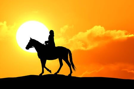 Silhouette or woman and horse running across horizon as the sun goes down. Stock Photo