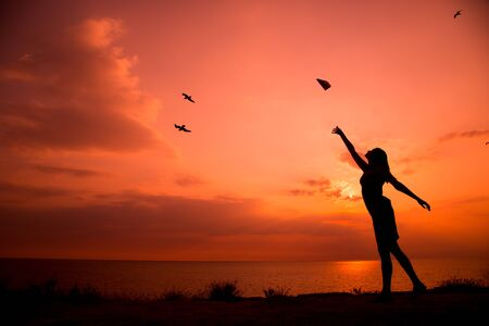 Beautiful silhouette of young woman throwing paper airplane. Standard-Bild