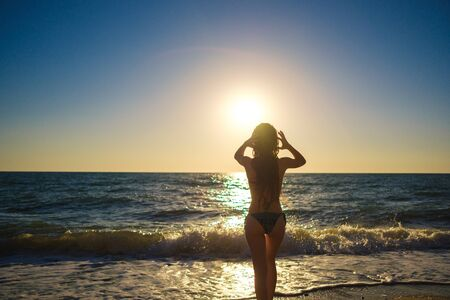 young slim beautiful woman on sunset beach, playful, dancing, running, bohemian outfit, indie style, summer vacation, sunny, having fun, positive mood, romantic, splashing water, silhouette, happy Stockfoto
