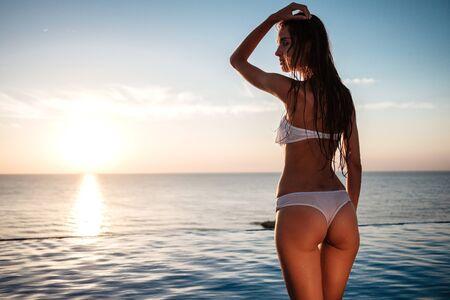 fashion outdoor photo of beautiful sensual woman with long dark curly hair in elegant white bikini relaxing beside swimming pool