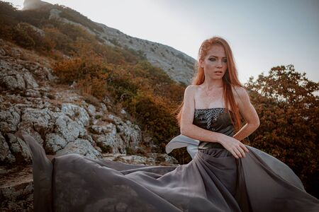 beautiful furious scandinavian warrior ginger woman in grey dress with metal chain mail. Woman is a Viking. Fantasy. Book Cover. beautifully flying dress