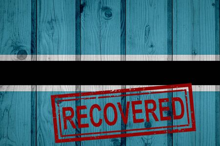 flag of Botswana that survived or recovered from the infections of corona virus epidemic or coronavirus. Grunge flag with stamp Recovered