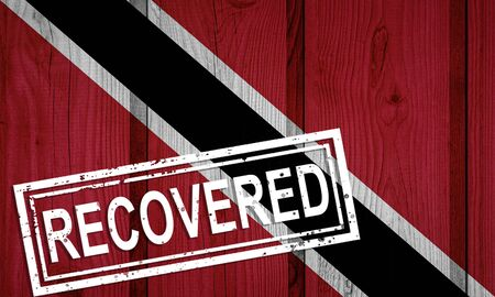 flag of Trinidad and Tobago that survived or recovered from the infections of corona virus epidemic or coronavirus. Grunge flag with stamp Recovered